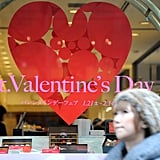 A woman walks in front of a cake shop displaying a St. Valentine's Day advertisement at a department store in the Ginza district in Tokyo.