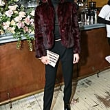 Bella, who showed off a similar smoky eye to Gigi, kept things dark in black separates, leather loafers, and an oxblood furry coat. Our favorite touch? Her playful braids mimicked the pattern on her own clutch.