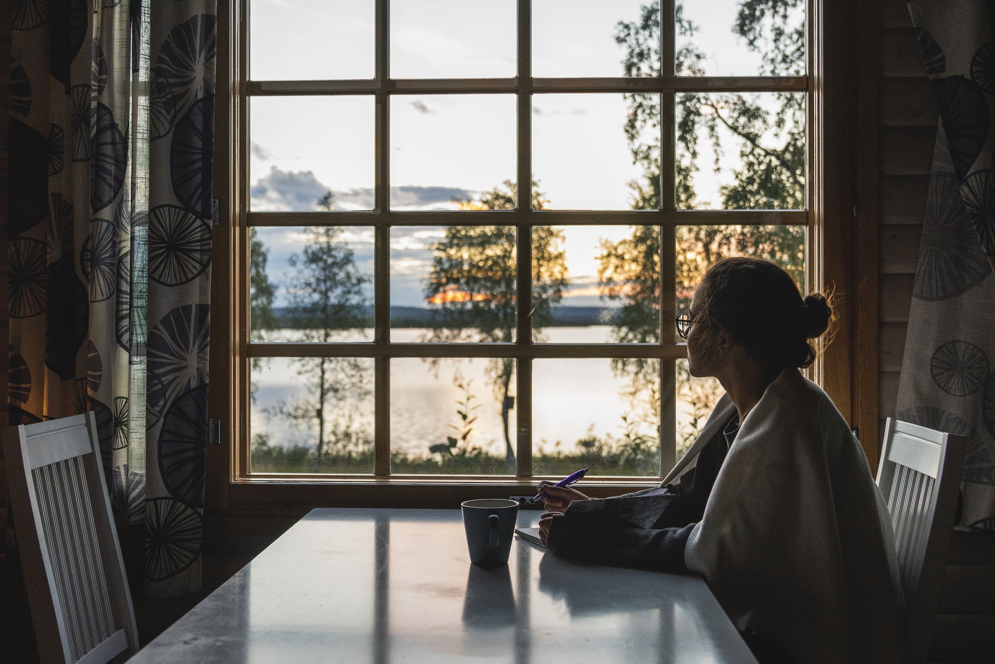 Finland, Lapland, young woman sitting at the window looking at a lake