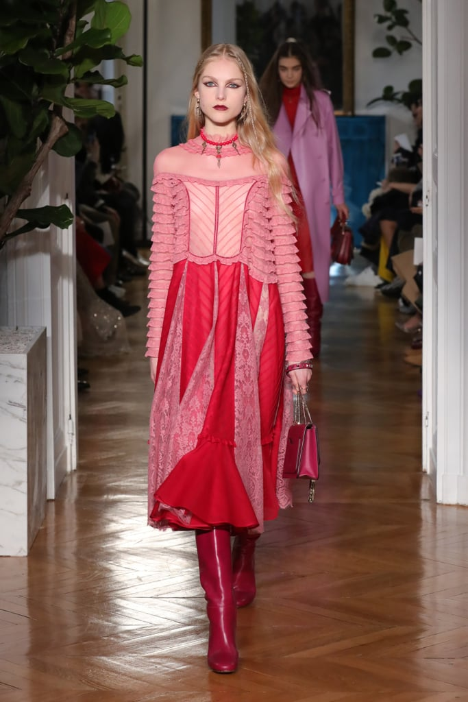 The next time you can't decide what to wear, look back at Valentino's Fall 2017 collection. Creative Director Pierpaolo Piccioli created the ultimate go-to uniform: shift dress with patent leather boots. Easy, right?  The designer sent billowy long-sleeved dresses in shades of red, blush, teal, and chartreuse down the runway, and every model wore an identical red beaded necklace. Boots were the shoe of choice, partly concealed underneath the hem of these everyday gowns. It's clear Piccioli has a penchant for romanticism, a quality the fashion house embodies, as almost every garment in the collection featured a high-neck collar and soft, lace details. Though the dresses were impressively beautiful, the outerwear also shouldn't be missed. Coats with split panels flowed away to reveal silky trousers and patterned dresses underneath. Several of these pieces featured abstract hand prints with mathematical equations. It was a funky design for the fashion house, though the pastel colours stayed true to the collection's aesthetics.  For the girl who loves black, however, do not worry, because Piccioli covered his bases by offering a mix of dark sheer and silky gowns (paired with boots of course) that were delightfully delicate.