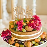 Azaleas, kumquats, and grapes are scattered among this naked layer cake.