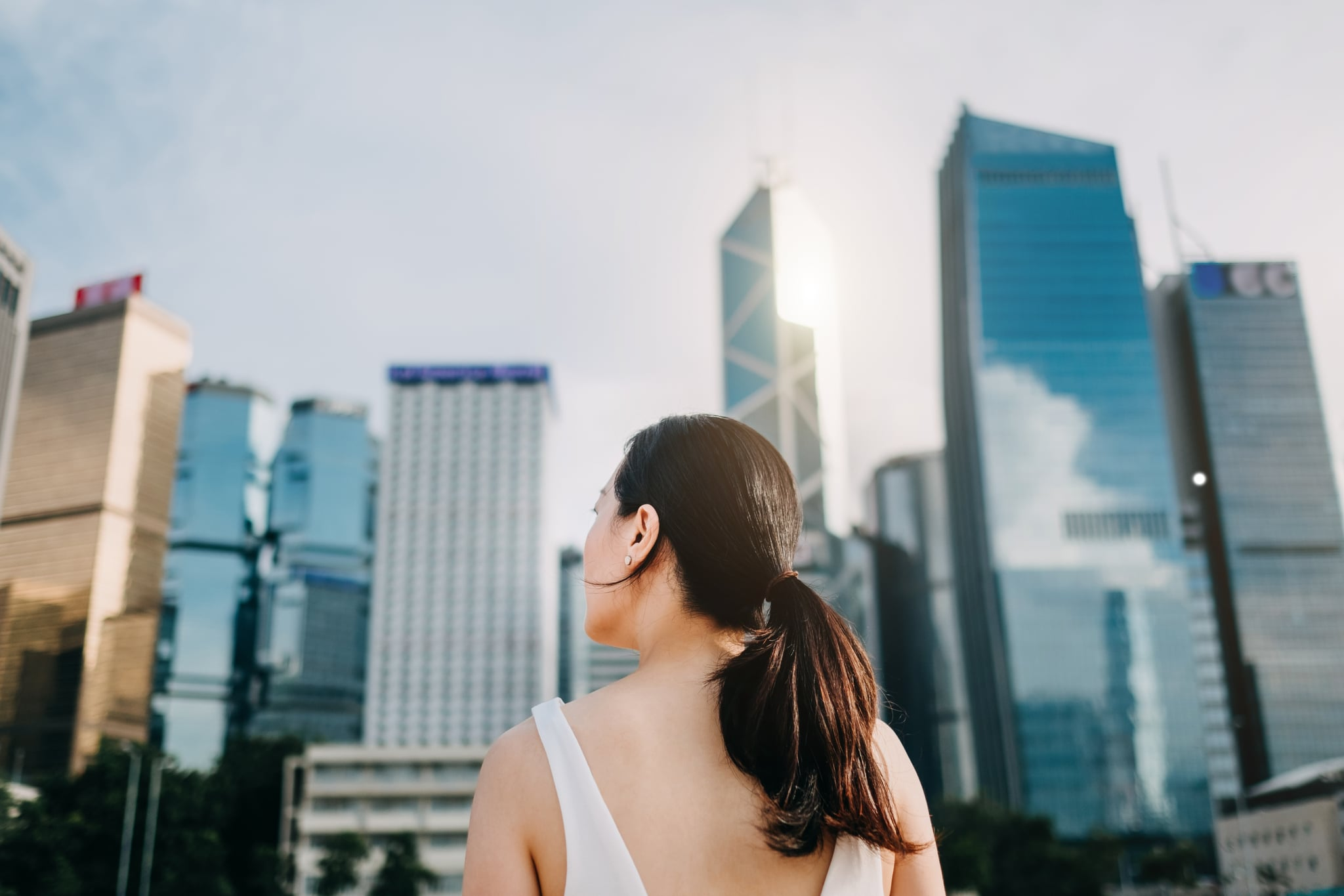 Rear view of ambitious businesswoman looking towards the urban financial towers in Central Business District