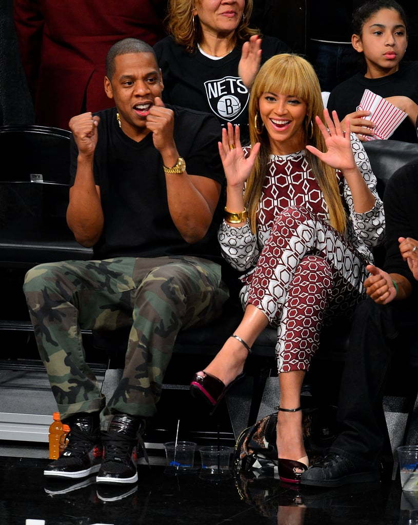 Beyoncé and Jay Z threw their hands up while checking out a Brooklyn Nets game together in November 2012.