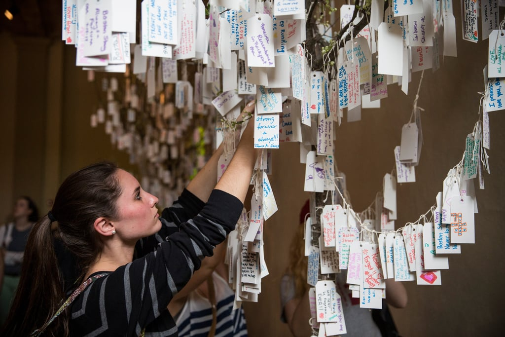 A woman hung her handwritten message on a tree of notes at the Boston Public Library's memorial exhibition.