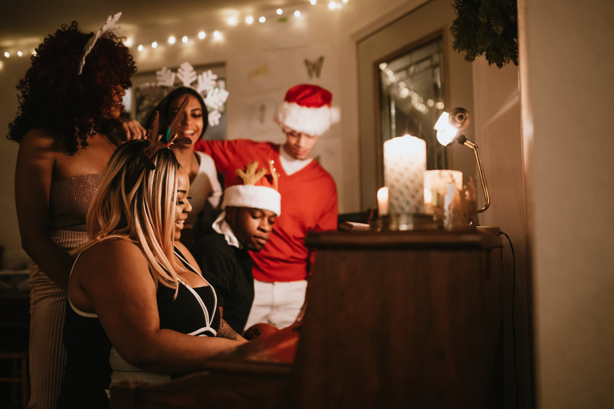 A group of young adult friends gather at a home for Christmas celebration over the holiday, dressed to fit the occasion with various Christmas accessories.  They sing songs together at the piano, enjoying the Christmas cheer.
