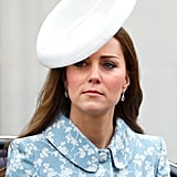 تتباين قبّعة كيت البيضاء من تصميم سيلفيا فليتشر وتقدمة متجر Lock & Co.  بشكلٍ صارخٍ مع معطف كاثرين ووكر المطبّع بالورود.