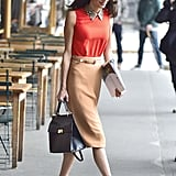 Amal wore a collared orange top with a beige knee-length skirt while out in NYC in 2015.