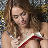 Miley writing in her diary.