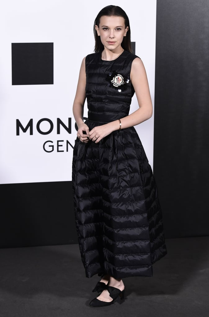 We can confidently say that Millie Bobby Brown was the most comfortable attendee at Milan Fashion Week. The exceedingly stylish 14-year-old attended the Moncler Genius show on Feb. 20 wearing a head-to-toe puffer gown from the brand. The simple look — well, simple for essentially being a sleeping bag dress — was only accented with Moncler's logo on the front. Though a daring look we might typically see on Rihanna, the Stranger Things actress pulled it off with ease, accessorizing with Repossi jewels and bow flats. It was an event brimming with creativity, after all: Moncler's newly launched Genius Project invites other designers and creative directors to create collections for the brand. The show Millie and other celebrities attended was the project's big debut. Ahead, get a closer look at the most comfortable gown we might ever lay eyes on.