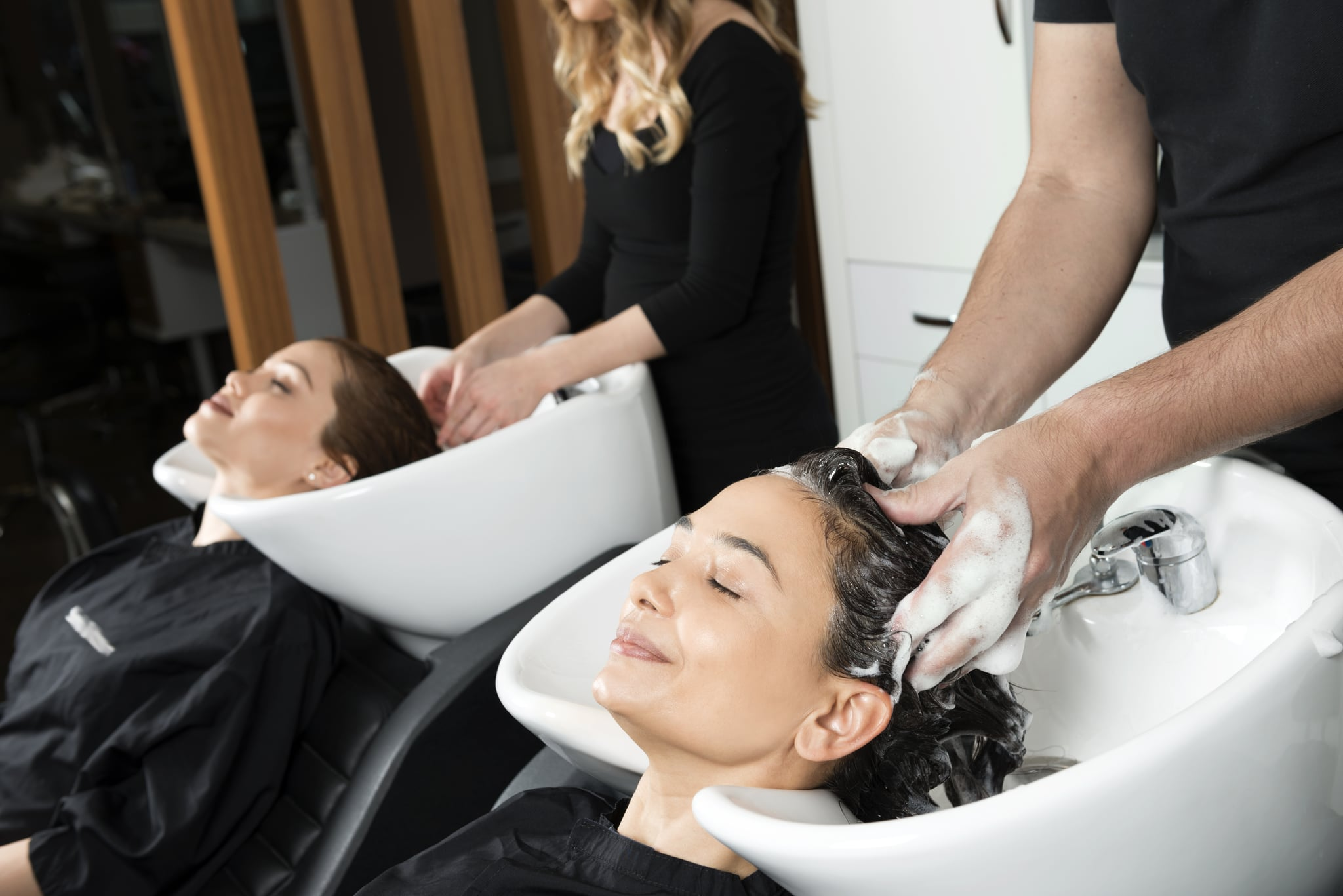 Hair washing section of a hairdresser's salon where two women are having their hair washed.