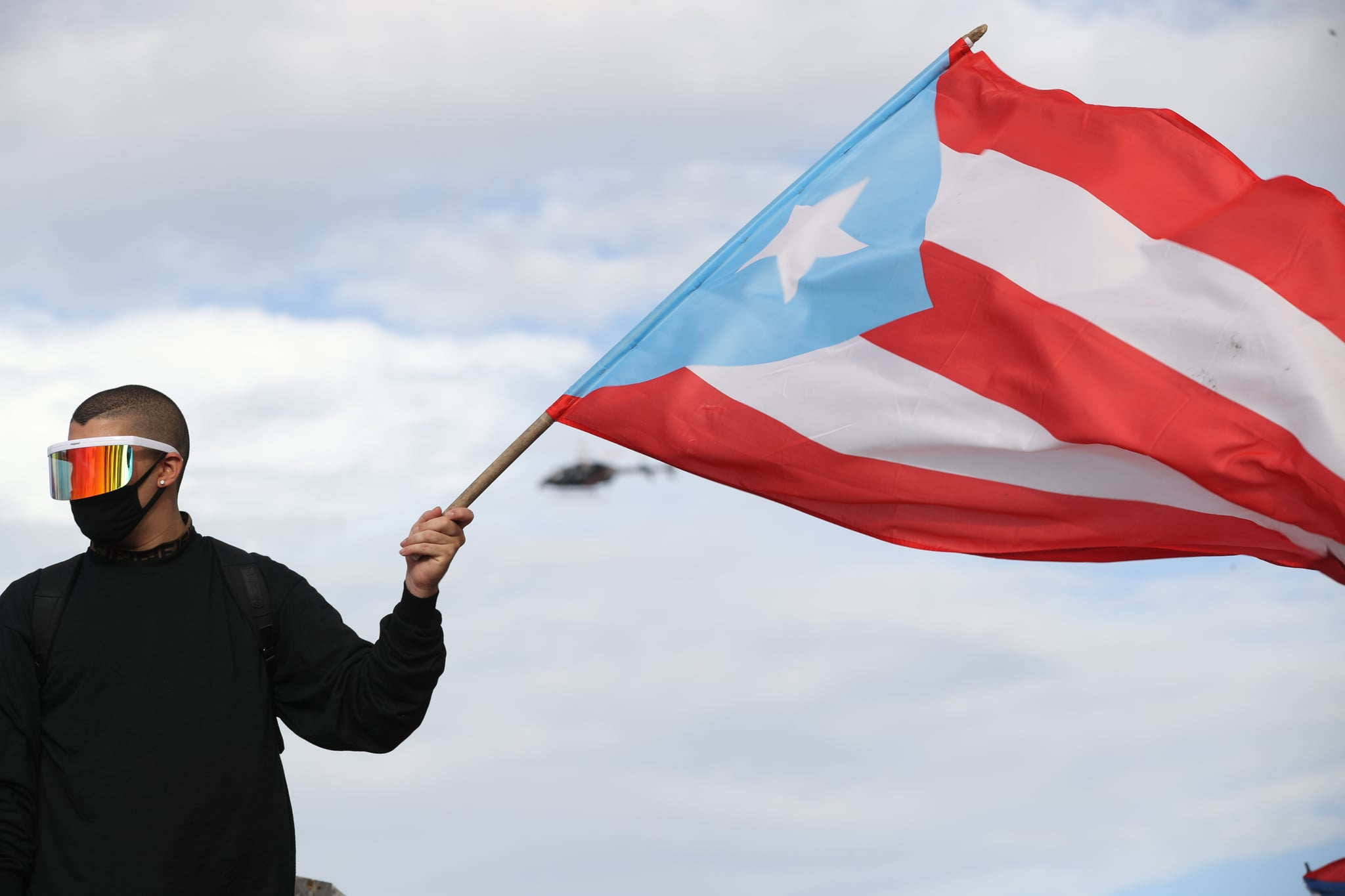 OLD SAN JUAN, PUERTO RICO - JULY 17: Reggaton singer and rapper Bad Bunny waves a Puerto Rican flag during protests against Ricardo Rossello, the Governor of Puerto Rico on July 17, 2019 in front of the Capitol Building in Old San Juan, Puerto Rico. There have been calls for the Governor to step down after it was revealed that he and top aides were part of a private chat group that contained misogynistic and homophobic messages. (Photo by Joe Raedle/Getty Images)