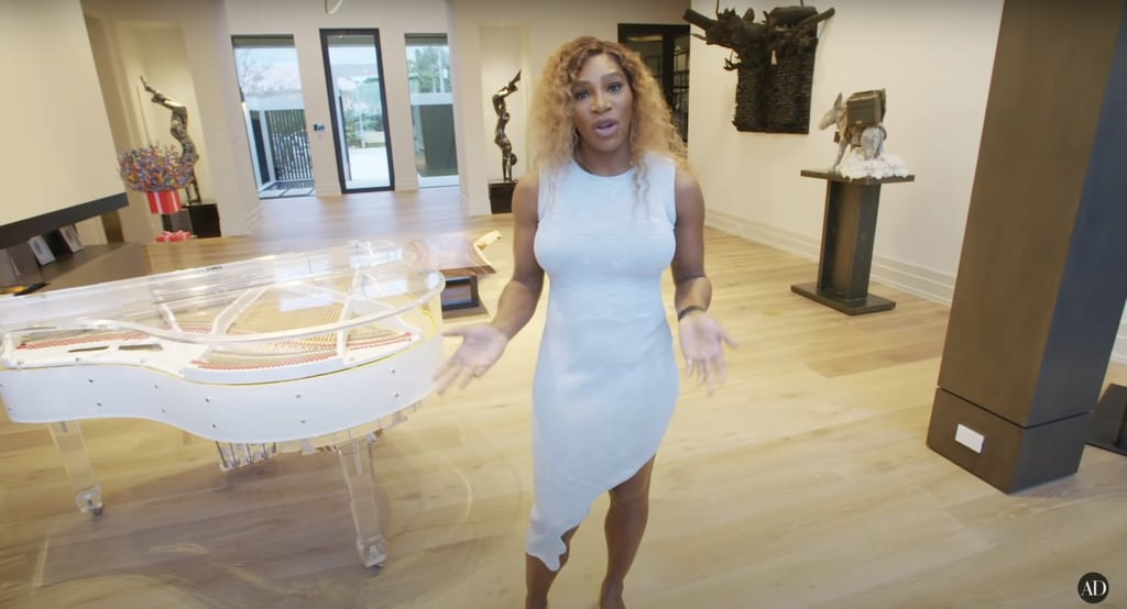 """When you're one of the most decorated athletes of all time, you've got to figure out where to put those trophies, right? Just ask Serena Williams! The multifaceted force of a human recently opened her doors to Architectural Digest for an inside look at her new Miami home, and we've got to say, it is outstanding. Not only does she have a massive room for all her trophies, but she hilariously revealed she doesn't keep second-place hardware. Legend! From the moment you enter Serena's home, you can immediately feel how much time she spent putting it all together. She swapped a living room for a modern art gallery and has a multifunctional karaoke room that could turn any shower singer like myself into Beyoncé.  """"Most homes actually have a formal living room, and I didn't want to lose that aspect, but I also didn't want a formal living room, and I was trying to decide what to do,"""" she says in the video. """"I love art and all kinds of artists, so I was like, 'What if I had a formal living room, but instead of it being a living room it's an art gallery?'"""" And that's exactly what she did. With pieces from Radcliffe Bailey, Kaws, and Brandon Marshall, she has truly built something spectacular.  Serena worked with sister Venus's interior-design company, V Starr Interiors, to bring her dream to life. With a clear Wurlitzer piano, a mural with an actual rock from the moon, and doors from Nepal, Serena clearly has a knack for interior decorating like her sister. The house is filled with sentimental items from her, Alexis, and Olympia's life together. Check out some close-up looks at the special details of Serena's new home ahead, from her art collection to her jaw-dropping trophy room and so much more.      Related:                                                                                                           Naomi Osaka Bought Her House From Nick Jonas, So of Course It's Massive — See Inside!"""