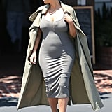 Kim stuck to her signature silhouette — a body-hugging tank dress and duster coat, this time in shades of tan and gray.