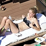 Brooklyn Decker adjusted her bikini top while laying out with a friend in Australia.