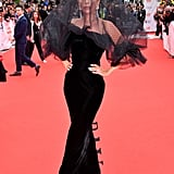 For the 2018 Toronto Film Festival, Lady Gaga wore an Armani Privé black gown, which she accessorized with a black veil, matching embellished hat, and Chopard jewelry.