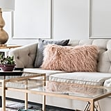 To create the glamorous look the homeowners wanted, Monica added dazzling accents, including a fuzzy pillow and gold-rimmed side table ($293).