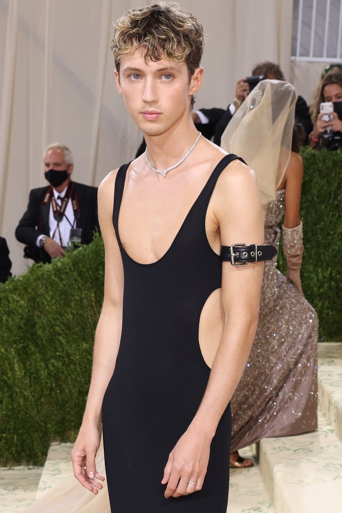 """Celebrity interpretations of the Met Gala's 2021 """"In America"""" theme ranged from gothic glam to elaborate and colourful on Monday night, but Troye Sivan's take is 100-percent New York City chic — with a sexy twist. Designed by Joseph Altuzarra for soon-to-be-launched """"genderful"""" brand ALTU, Troye's black knit dress featured sleek side cut-outs and a plunging neckline that perfectly showed off his collarbones. In speaking with Vogue's red carpet host Keke Palmer, Troye said his inspiration for the look came from his vision of America, which stems strongly from NYC street style, minimalist designs, and classic black and white colour schemes.  The """"Angel Baby"""" singer added a bit of sparkle to the figure-hugging look with a Cartier diamond necklace and a black leather armband on his left bicep, a sexy shoutout to his new visualizer video. While his dress stretched almost all the way down to the carpeted Met Gala steps, we did get a peek at his futuristic four-inch platform boots with a transparent heel. We can only imagine what it was like navigating the sea of selfies and extravagantly-dressed celebrities in those shoes, but Troye made the entire outfit look effortlessly elegant.  See his outfit from all angles ahead and check out some more of our favourite Met Gala ensembles here.      Related:                                                                                                           Billie Eilish Agreed to Wear This Met Gala Gown Under 1 Condition: Oscar de la Renta Stops Using Fur"""