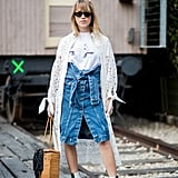 Throw a Knee-Length Eyelet Coat Over a White Tee and Denim Skirt