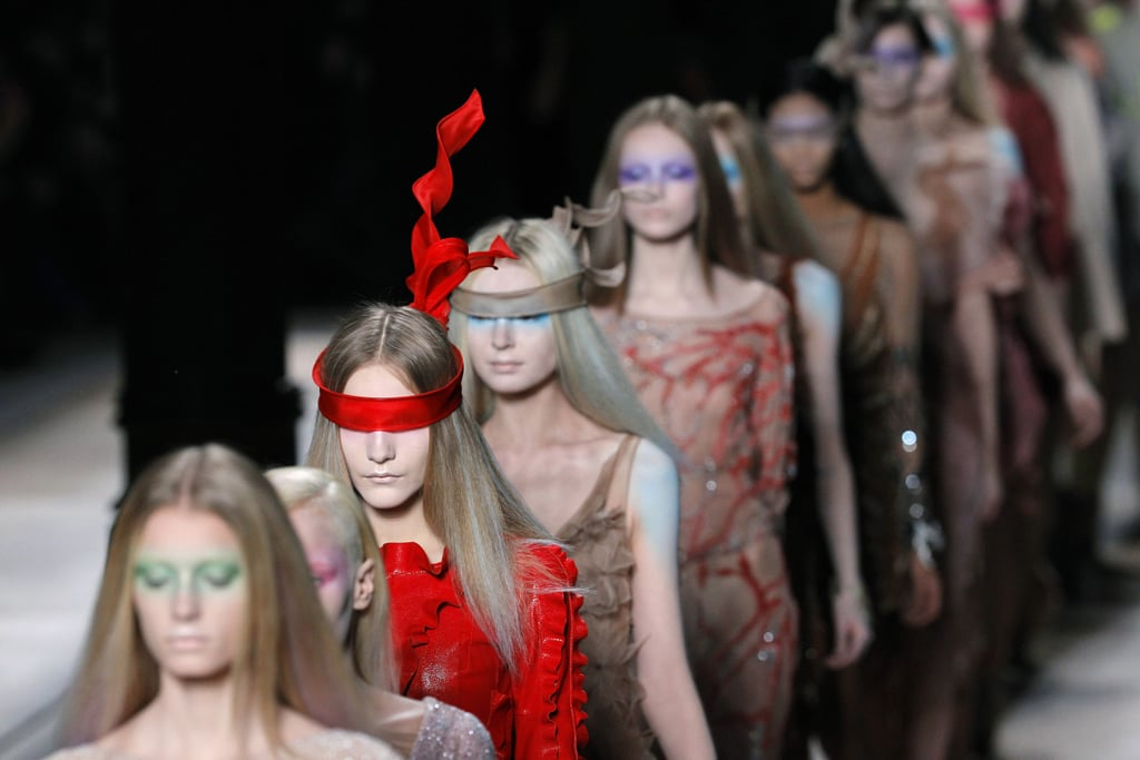 """>> A year after Maria Grazia Chiuri and Pier Paolo Piccioli dropped their first Valentino couture collection — an ode to the archives — the designers have entirely switched direction. """"We think that to keep a future in couture, it's necessary to bring a new customer who wants something cooler,"""" Chiuri said backstage. Piccioli added, """"We tried to make new strategies for going forward. To do that we have to experiment with new silhouettes . . . because we want to call the young girls. They can be new customers for couture because they want beauty, they want personalized things."""" This injection of youth involved Alice Dellal walking the runway and sheer ribbon blindfolds created by Philip Treacy; the graphically colorful collection is already earning comparisons to Nicolas Ghesquiere's Balenciaga, with some terming it """"Valenciaga."""" But Piccioli says the collection is """"about a woman wandering in this beautiful Eden. It's a dream. Couture is a dream."""""""