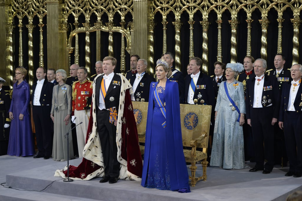 King Willem-Alexander and Queen Maxima of the Netherlands stood in front of their thrones near members of the royal household during their inauguration ceremony at New Church in Amsterdam.
