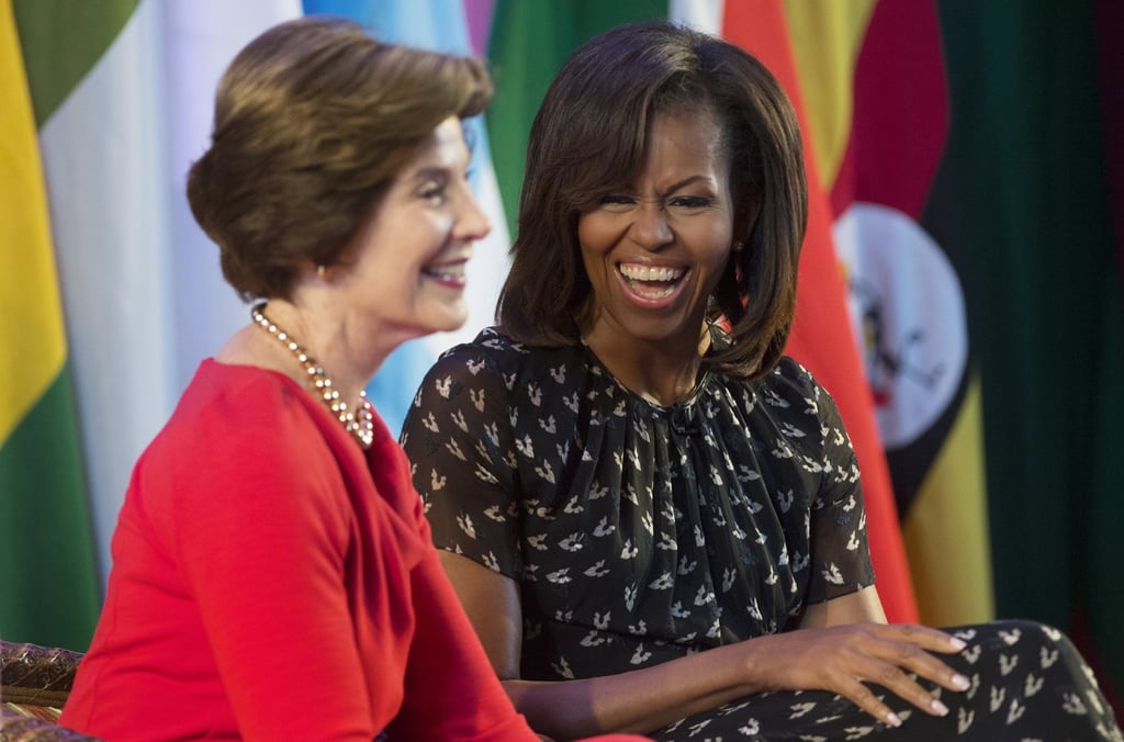 First Lady Michelle Obama laughed alongside former First Lady Laura Bush at the African First Ladies Summit in Dar es Salaam, Tanzania, in July 2013.