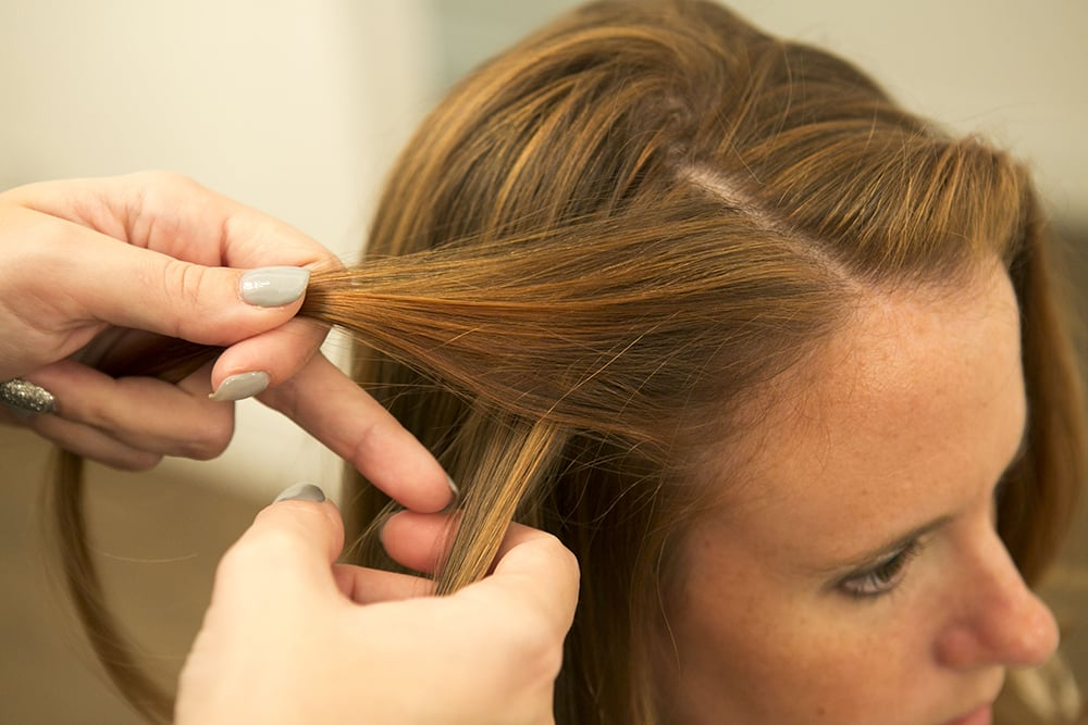 Cross the section of hair along your hairline over the other section, so it's going away from your face.