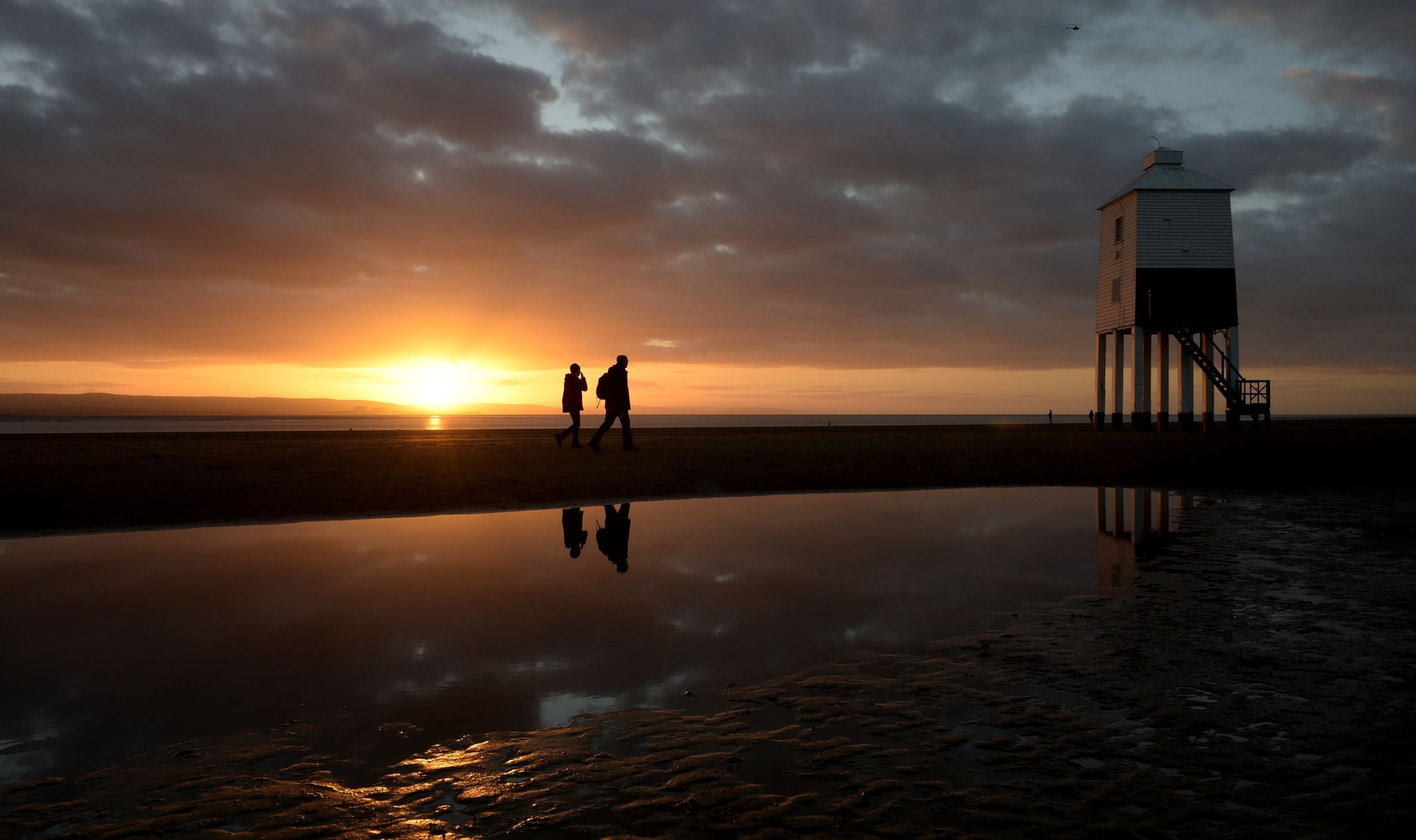 People walk past the lighthouse at Burnham-on-Sea, Somerset, as the sun sets an hour earlier after the clocks went back one hour last night due to the end of Daylight Saving Time and the switch from British Summer Time (BST) to Greenwich Mean Time (GMT). (Photo by Ben Birchall/PA Images via Getty Images)
