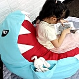 The pocket in the fin of the Lmeison Animal Storage Bean Bag Chair ($24) can hold books, toys, or even snacks!