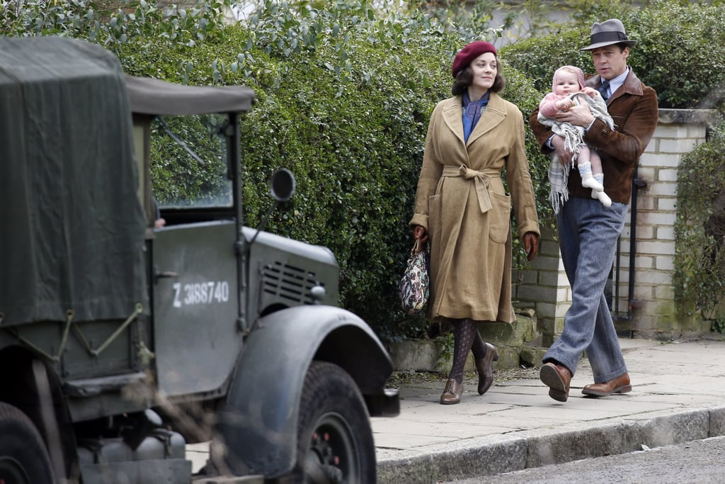 Brad Pitt and Marion Cotillard hit the set of their new film, Five Seconds of Silence, in London on Thursday. The pair were spotted shooting scenes with a supercute baby girl, and Brad played the role of doting dad — something we're sure he's got lots of experience with — by cradling the little one and carrying her high on his shoulders as Marion held on to a picnic basket. The romantic thriller, which is being directed by Robert Zemeckis, is reportedly set during World War II and follows a spy who falls in love with a French agent during a mission in North Africa. Last time we saw Brad was in January, when he was wearing a decidedly more modern outfit and putting his charm on display with Ryan Gosling on stage at the Golden Globes. Is it just us, or does he look even younger than he did then? Almost as if he's . . . Benjamin Button-ing himself? Keep reading to see Brad looking youthful and being really, really sweet with a baby on set.