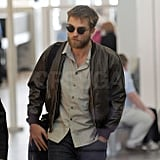 Robert Pattinson wore a leather jacket and sunglasses arriving at LAX.
