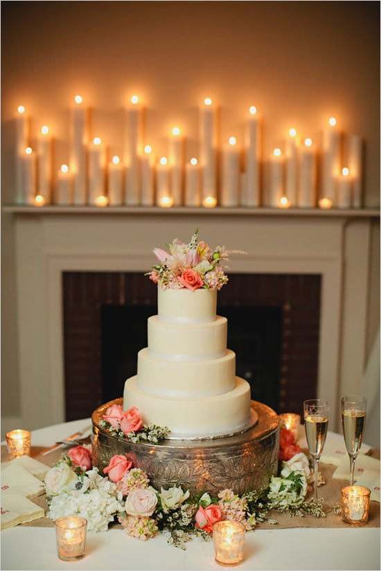 This is the perfect example of how you can take a plain tiered cake and turn it into a dessert with flair. Here, the extra details — the stand, the candles, the flowers — make it stand out, but it could just as easily look great without them.  Photo by Kristyn Hogan via Wedding Chicks