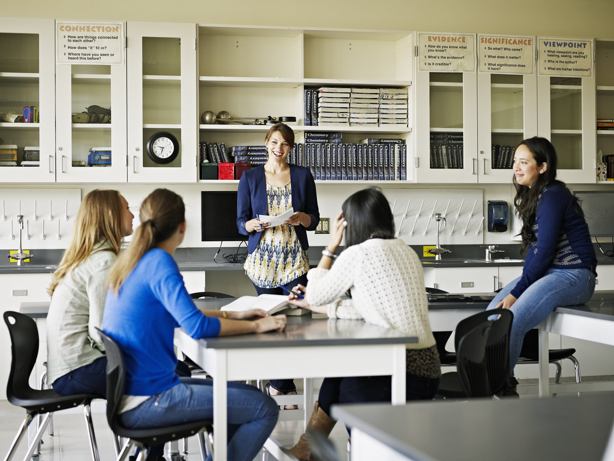 Female teacher standing in science lab classroom in discussion with a group of female students