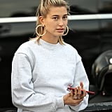 Overemphasize your earring shape when you work a pair with simple sweats and tie up your hair, just like Hailey Baldwin.