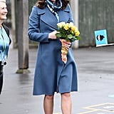 During a visit to the Roe Green Junior School, Kate wore a blue Sportmax coat, which she accessorized with a printed Beulah London scarf.