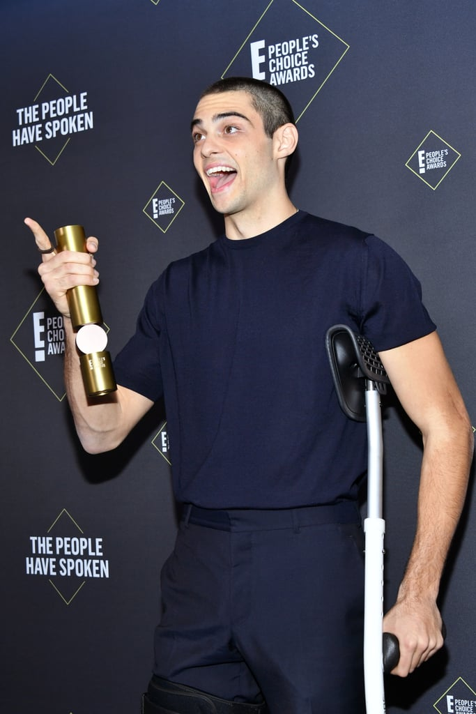 "Despite recently undergoing knee replacement surgery, Noah Centineo still brought positive energy to the 2019 People's Choice Awards on Sunday. The actor arrived at the award show wearing a brace and relying on a crutch after undergoing surgery as a result of dislocating his knee during a basketball game in October. He's since continued to offer insight into his postsurgery routine, including a ""ridiculous shower adventure,"" on Instagram Stories. Fortunately, Noah didn't go home empty-handed, as his endearing performance in The Perfect Date earned him the award for comedy movie star of the year. In his unexpectedly serious speech, Noah left viewers with this message: ""It matters not what you've done, but what you do with what you've done for others."" Watch the speech and see pictures from his award show appearance ahead."