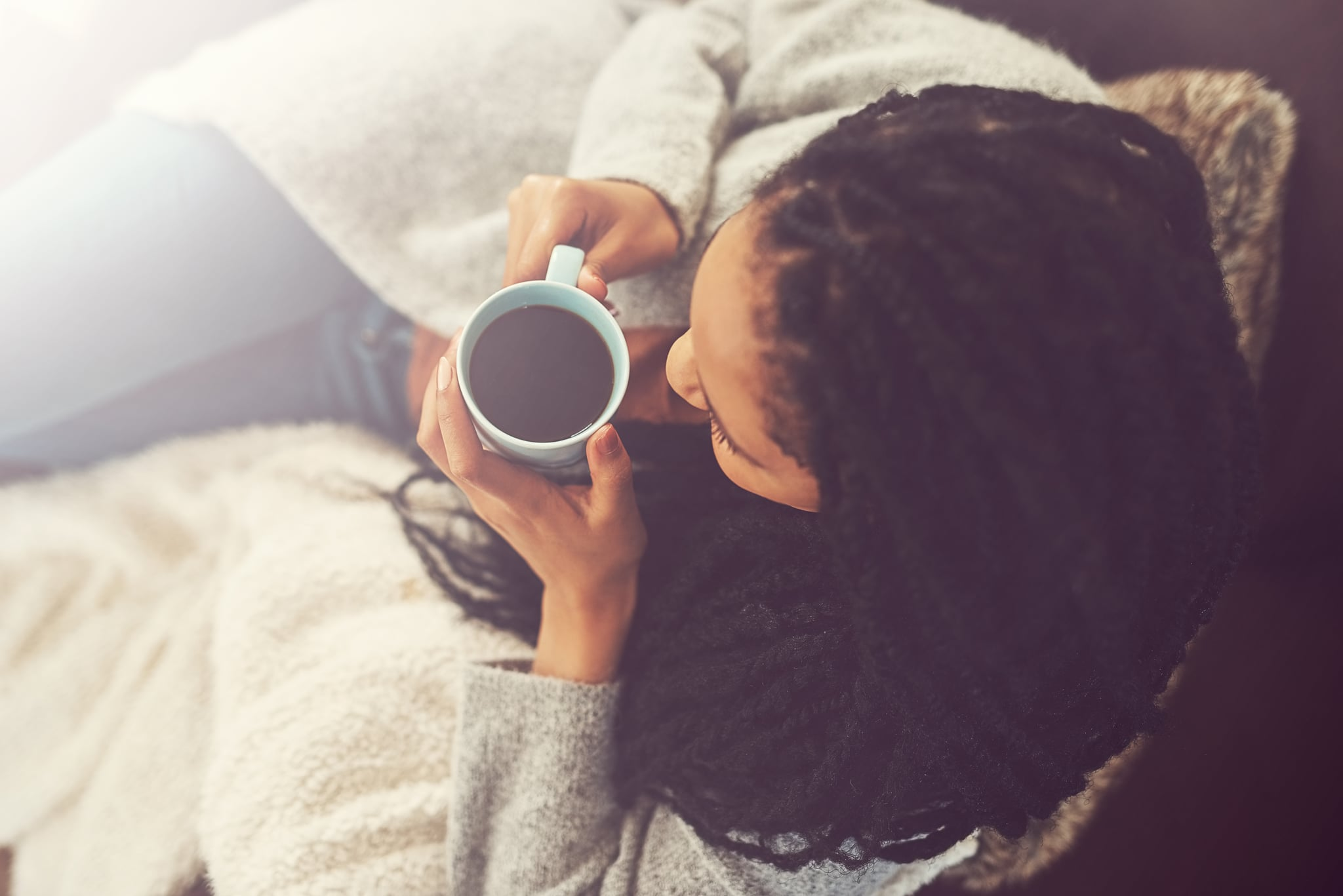 Shot of a young woman enjoying a cup of coffee at home