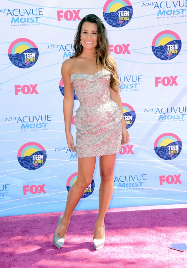 "The Teen Choice Awards have kicked off! Lea Michele was one of the first to hit the pink carpet and she chose a short, silver Versace dress for the occasion. Lea tweeted herself in the hair and makeup chair, saying ""it takes a village"" to get ready. The actress is nominated for two surfboard trophies today: choice female movie scene stealer for New Year's Eve and choice TV comedy actress for Glee. Her Glee co-star Kevin McHale is hosting the festivities with Demi Lovato. Stay tuned for more from the Teen Choice Awards, and tell us what you think of Lea's look."