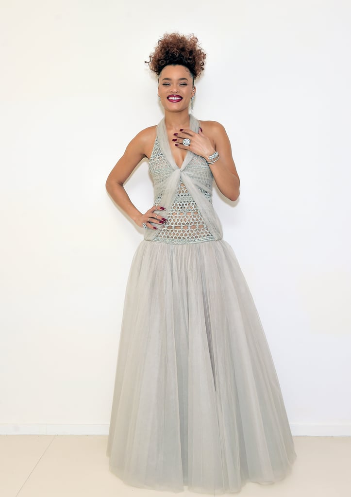 "Andra Day's elegant look at the 2021 Golden Globes was as timeless as the music of Billie Holiday. The singer and actress, who is nominated for her portrayal of the jazz legend in The United States vs. Billie Holiday, wore a floor-length Chanel gown from the brand's recent spring couture show. The dress featured a full skirt and crocheted bodice with tulle panels. Styled by Wouri Vice, the outfit was completed with glimmering bangles, statement rings, and an ear cuff — also by Chanel — and custom Stuart Weitzman heels.  Though she chose Chanel for the red carpet, Andra mostly wore vintage pieces and Prada in the Lee Daniels-directed film. In an interview with POPSUGAR, costume designer Paolo Nieddu spoke about how the 1950s outfits helped Andra transform into Billie. ""She understands the period and the way the clothes are supposed to be, so when she would try things on in fittings, she transformed and threw herself into it from a style standpoint. She knew how to move in them,"" he said. ""When you wear vintage, it's different than now, and I think Andra really understood that, and that helped sell the garment."" See photos of the star looking absolutely timeless at the Golden Globes ahead.       Related:                                                                                                           Dan Levy Is Wearing So Much Color to the Golden Globes, David Rose Could Never"