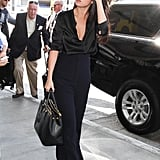 Fall staple: a long-sleeved silky blouse. Selena wore it with: High-waisted trousers and a black Prada tote bag at LAX in August 2015.