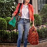 For a rain scene, Selena covered up her outfit with a coral bomber jacket and carried a green St. Louis GM from Goyard tote.