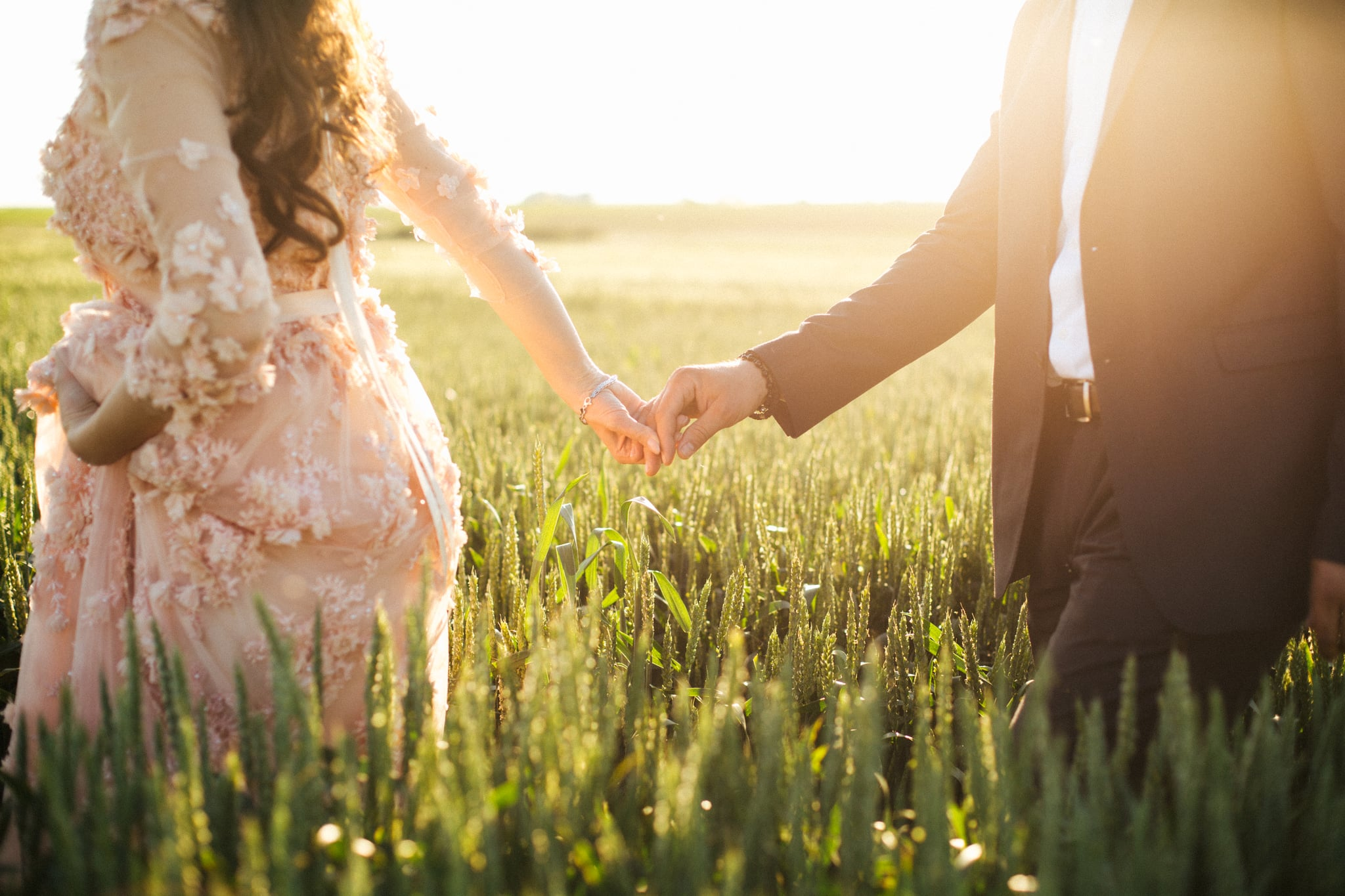 Bride holding grooms hand in field full of wheat
