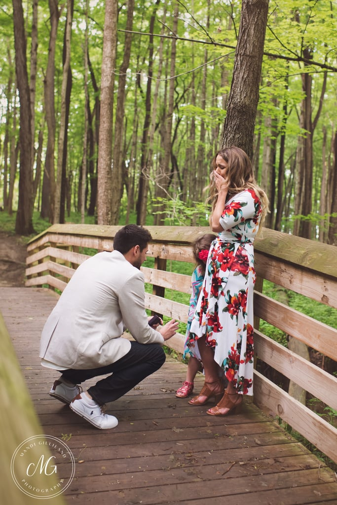 """Get ready to weep, y'all. In what may be the sweetest proposal we've ever seen, a single mom who found the man of her dreams got a huge surprise when her boyfriend got down on one knee in the middle of a gorgeous nature preserve. However, Grant had an even bigger surprise in store — after he asked Cassandra to marry him (and she said yes!), he then got down in front of her young daughter, Adrianna, and asked the little girl if he could be her daddy. Photographer Mandi Gilliland, who has been friends with Cassandra for years, popped out of hiding to capture both magical moments between the trio, and the photos are absolutely stunning. """"I saw Cassandra's journey from the very beginning as a single mom raising Adrianna on her own,"""" Mandi told POPSUGAR. """"Witnessing all of the trials she had to overcome was heartbreaking, yet encouraging. Of all the things she had to walk through, she never gave up hope that one day she would find a loving and positive father for her daughter. As soon as Cassandra met Grant, we all knew instantly that this one was going to be her ever after. Once Grant reached out to me and expressed what he wanted to do for Cassandra and Adrianna, I was beyond ecstatic!"""" In a post to How He Asked, Cassandra described Grant's proposal to her as one of the best moments of her life but had so much more to say about his """"proposal"""" to her daughter: After proposing to me, Grant got back down to propose to my daughter. He said, """"Adrianna, can I be your daddy, to promise to love and protect you for the rest of your life?"""" As soon as he spoke those sweet words, I once again broke down in tears. Not the cute kind of tears either, the bawling type tears. My little heart could not take so much love! My daughter replied in complete shock, """"Thank you!"""" (As she has always been raised to use her manners when given a gift.) Grant then asked her, """"Is that a yes or no, sweetheart?"""" She replied, """"YES!"""" and then screaming with joy she said, """"I FINALLY GET A DADDY, MOMMY, I """