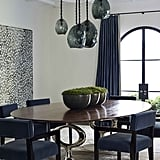 A custom dining table and chairs rest below dramatic pendant lights by David Wiseman.