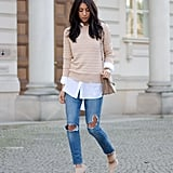 A blush sweater layered over a white shirt, jeans, and matching heels.