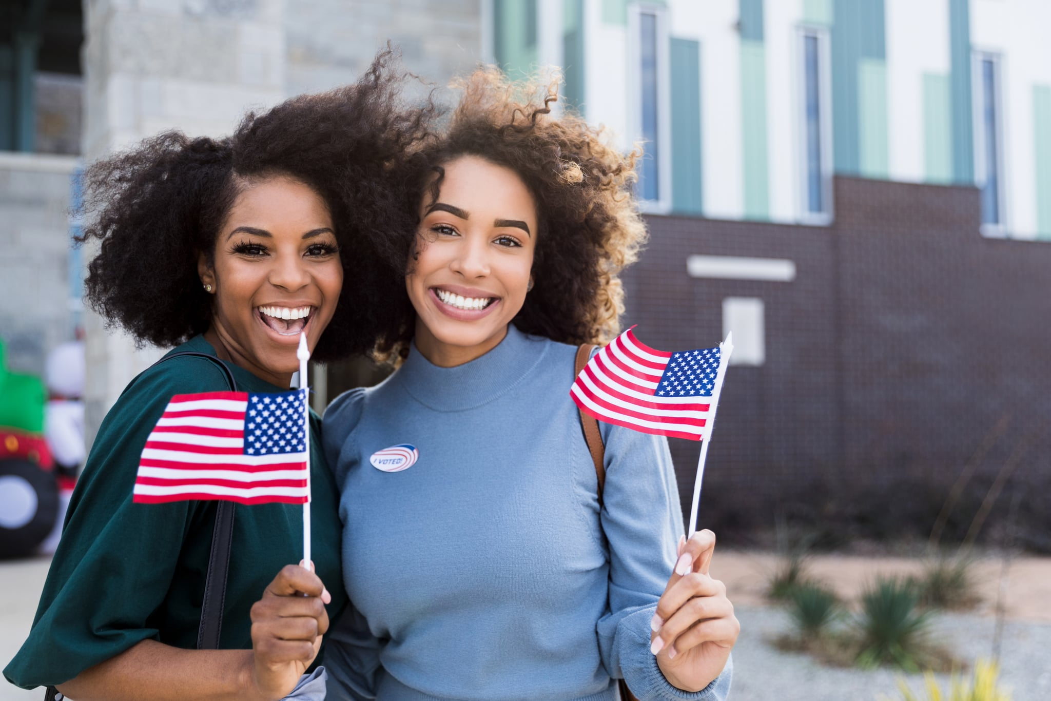 Two mid adult female friends stand together waving their American flags after voting.  They are outside the polling place.