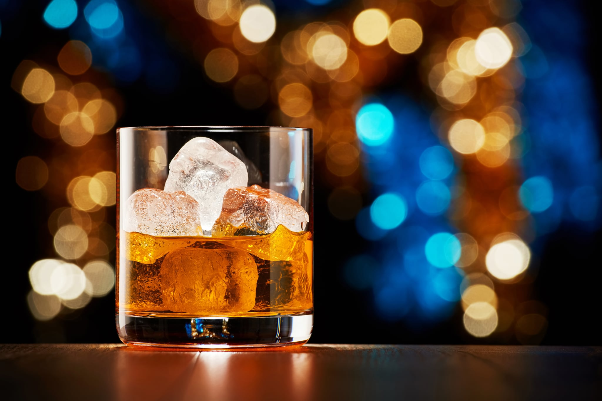 Glass of whiskey with ice on colourful Christmas lights bokeh background
