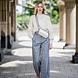 Take a cue from this street style star and accentuate the slimming effect of high-waisted pants by tucking everything in — even a chunky knit. This look is perfect for the office.