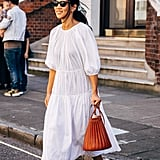 Style a simple parachute dress with a silk bow in your hair and leather glove pumps.