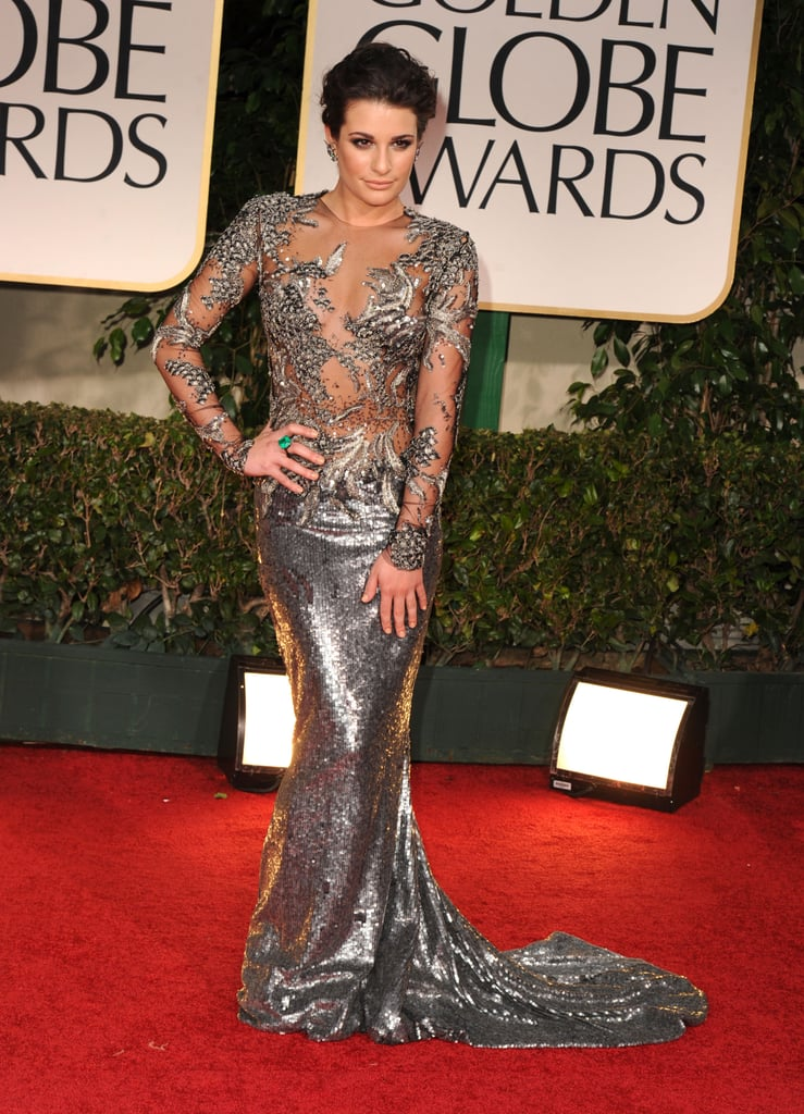 Glee star Lea Michele showed a little skin in a revealing metallic Marchesa fishtail gown. The sheer and embellished details on top covered Lea Michele in all the right places, while the shimmery train was an ultra-shiny, body-hugging silhouette. She complemented the look with an emerald cocktail ring and costume-jewelry-inspired earrings.