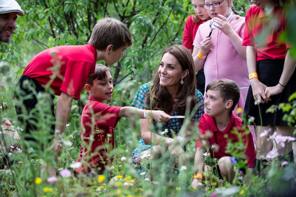"Kate Middleton is growing quite a green thumb this Summer. Her Back to Nature garden reopens at the Hampton Court Palace Garden Festival, where on Monday afternoon the Duchess of Cambridge invited children from four different charities to enjoy a treasure hunt, insect spotting, and a picnic. Kate first introduced her Back to Nature garden — which she co-designed with landscape architect Davies White and the Royal Horticultural Society — at the Chelsea Flower Show. The original garden featured a tree house and rope swing — which the duchess' children Prince George, Princess Charlotte, and Prince Louis thoroughly enjoyed — edible plants, and flowers to be used for crafts. The interactive garden was so successful that the Duchess brought the same concept to the Hampton Court Palace Garden Festival, but on an even larger scale. The garden at Hampton Court Palace is reportedly double the size of the one at the Chelsea Flower Show and includes a new hidden burrow, rolling hill, and stream. For an afternoon playing outdoors, the duchess ditched the casual white sneakers and wide-leg khakis she wore to the Chelsea Flower Show and instead went with a simple-yet-elegant green Sandro dress, a pair of affordable Accessorize earrings (that are now sold out, naturally), and her go-to espadrille wedges she's been rocking all Summer. The Duchess took the children through the garden space, where she helped them look for bugs and pointed out different types of flowers. Prince George gave the garden at the Chelsea Flower Show a ""10 out of 20."" We wonder what he'll have to say about this one."